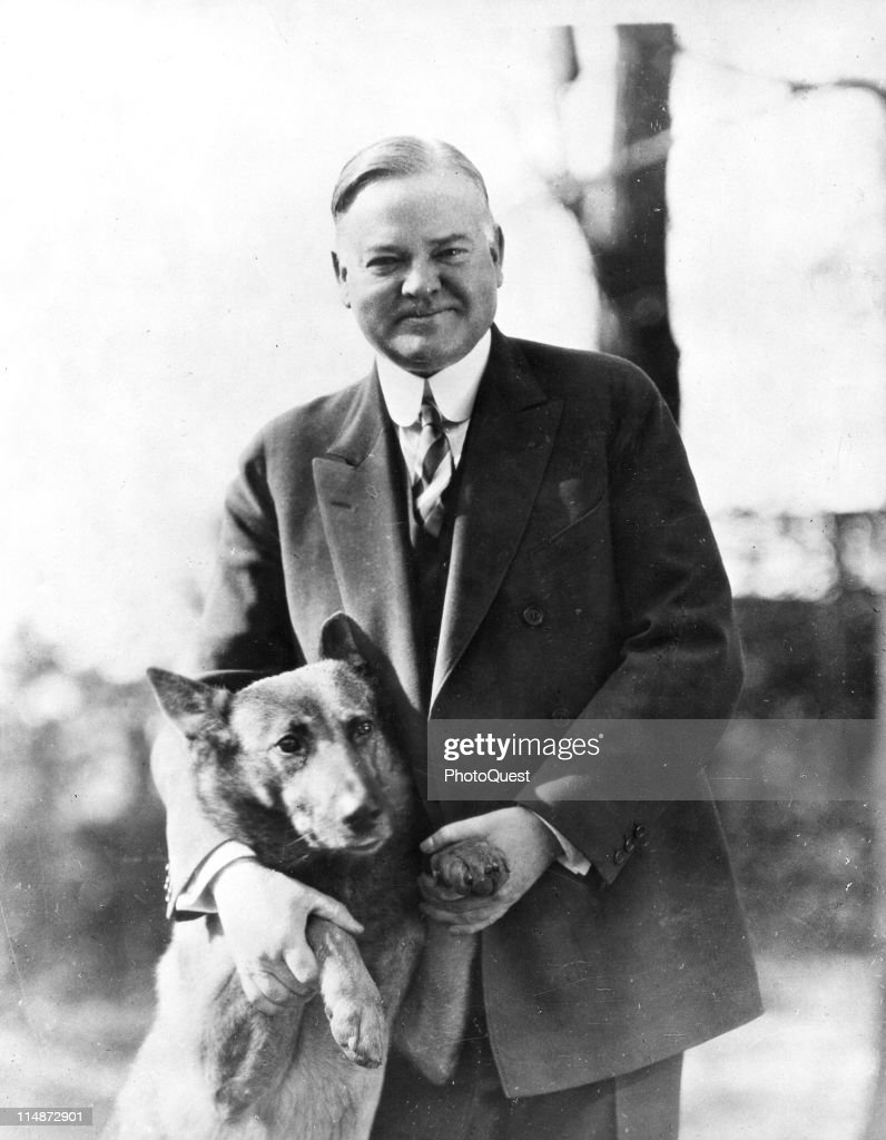 Portrait of American President Herbert Hoover (1874 – 1964) as he poses with his pet dog King Tut, 1930s.