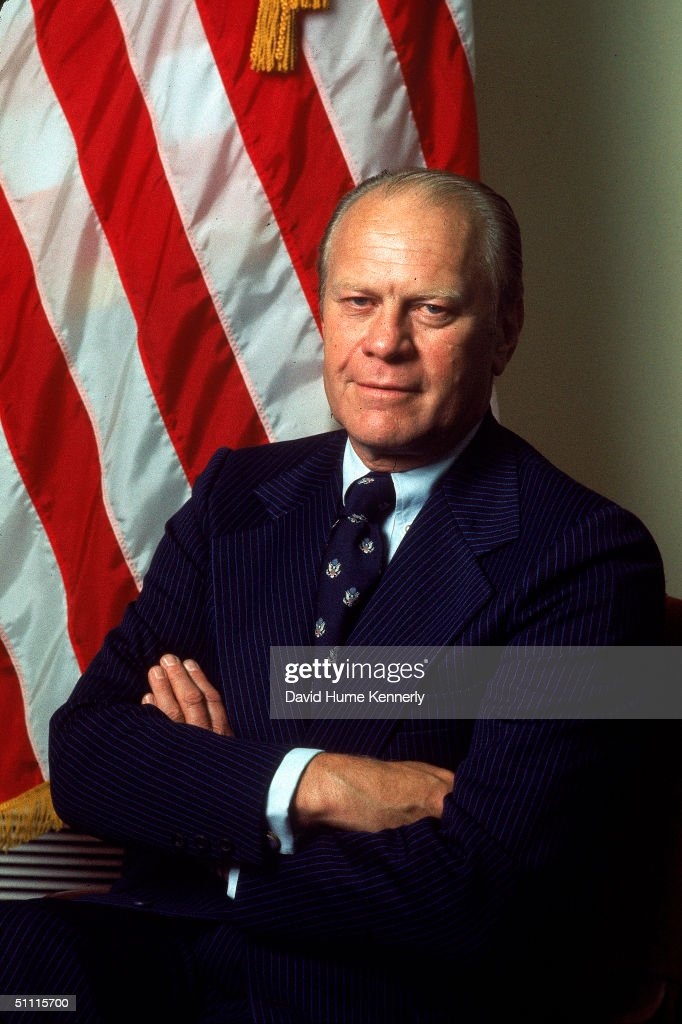 Portrait of American Presisdent Gerald Ford dressed in a blue, pin-striped suit as he stands with his arms crossed, taken during his first month in office, August 1974.
