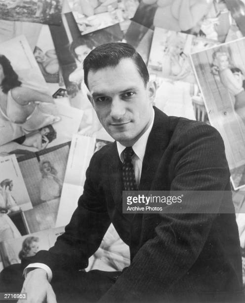 Portrait of American publisher Hugh Hefner sitting in front of a wall collage of female centerfolds from his men's magazine 'Playboy' which he...