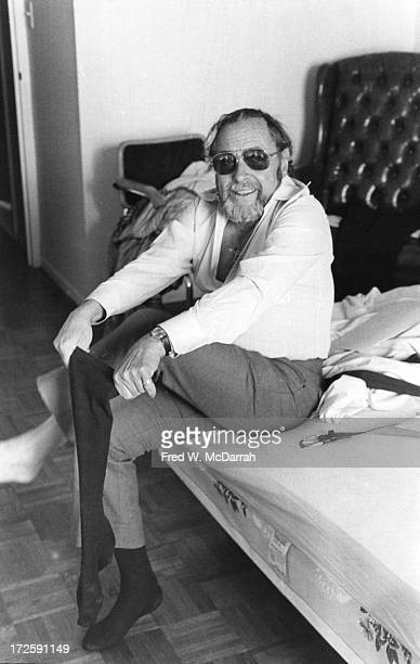 Portrait of American Pulitzer Prize-winning playwright Tennessee Williams as he sits on a bed in his apartment and puts on a sock, New York, New...