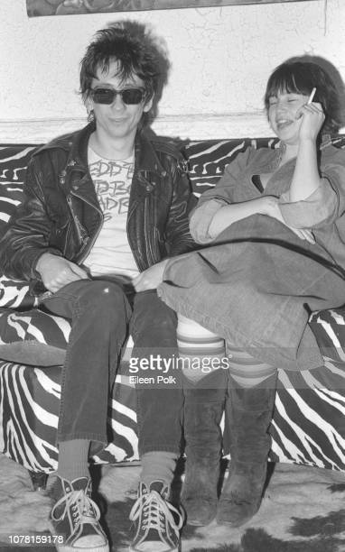 Portrait of American Punk musician Stiv Bators of the group Dead Boys and visibly pregnant Damita Richter as they sit on a zebrastripe couch in the...