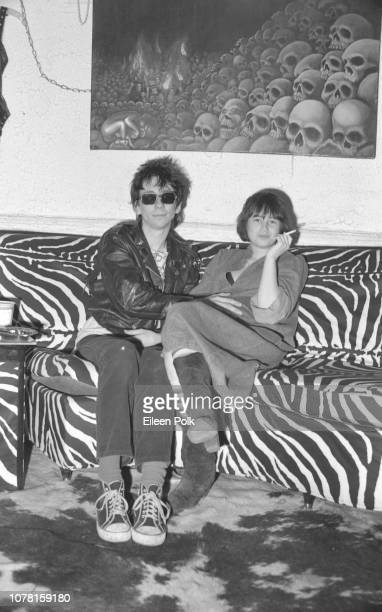 Portrait of American Punk musician Stiv Bators of the group Dead Boys as he sits with one hand on the stomach of visibly pregnant Damita Richter on a...