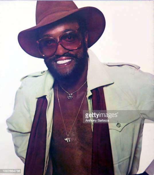 Portrait of American RB and Soul musician Billy Paul dressed in a hat sunglasses and a scarf with his shirt unbuttoned as he poses against a white...