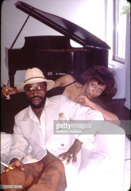 Portrait of American RB and Soul musician Billy Paul dressed in a hat sunglasses and a long white jacket as he poses on a sofa with an unidentified...