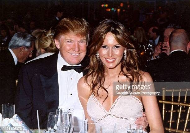 Portrait of American real estate developer Donald Trump and his girlfriend model Melania Knauss as they smile during a New Year's party at the...