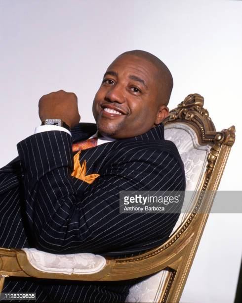 Portrait of American record executive Kevin Liles in a pinstripe suit as he sits in an armchair New York 1990s