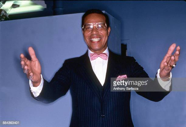Portrait of American religious leader Louis Farrakhan as he grins and stands with his arms outstretched New York 1984