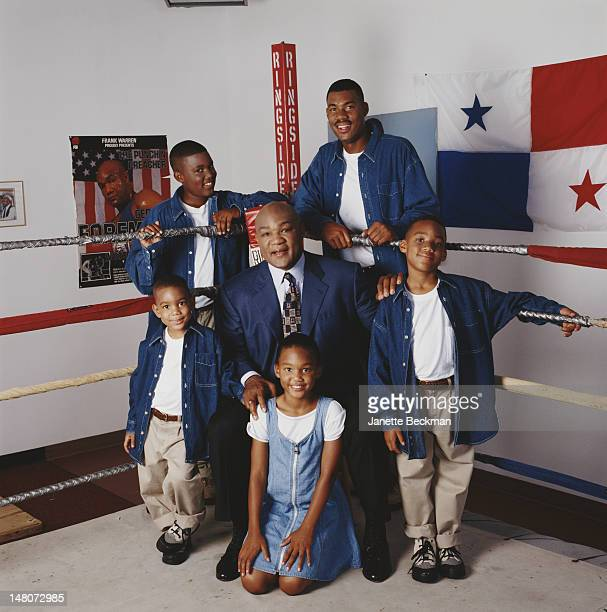 Portrait of American retired boxer George Foreman as he poses in a boxing ring with four of his sons and one of his daughters, Texas, 2003.