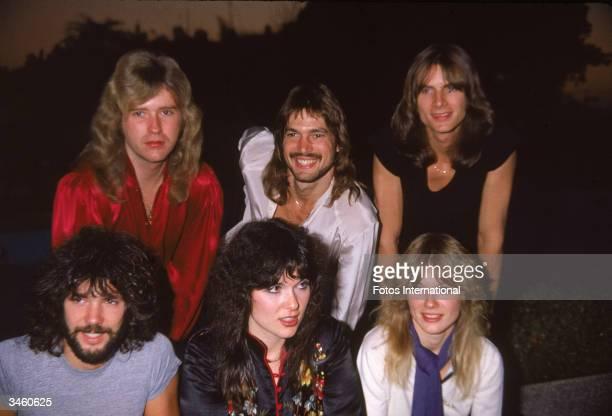Portrait of American rock band Heart sitting outdoors including Howard Leese Roger Fisher Steve Fossen Nancy Wilson Ann Wilson and Michael DeRosier...