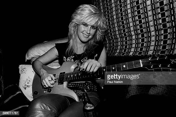 Portrait of American Rock musician Lita Ford as she poses with a guitar in her tour bus Chicago Illinois September 30 1984