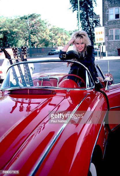Portrait of American Rock musician Lita Ford as she poses with a Corvette sports car at a gas station Chicago Illinois September 30 1984