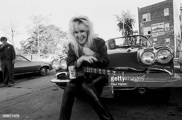 Portrait of American Rock musician Lita Ford as she poses with guitar and a Corvette sports car at a gas station Chicago Illinois September 30 1984