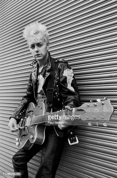 Portrait of American Rockabilly and Rock musician Brian Setzer of the group Stray Cats as he poses with his guitar backstage at the Marcus...