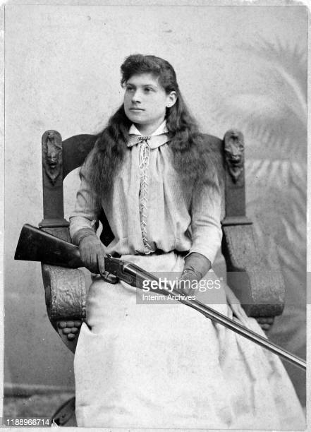 Portrait of American sharpshooter Annie Oakley as she sits in a carved wooden chair with a rifle over her lap, 1880s.