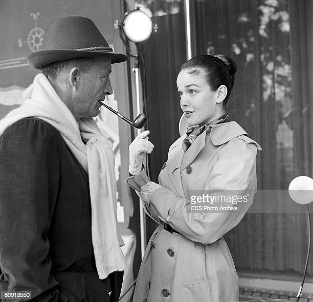 Portrait of American singer and actor Bing Crosby talks with his wife actress Kathryn Grant Crosby off stage during the filming of his television...