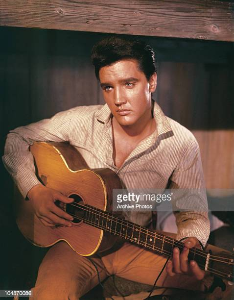 Portrait of American singer and actor Elvis Presley holding an acoustic guitar circa 1956.