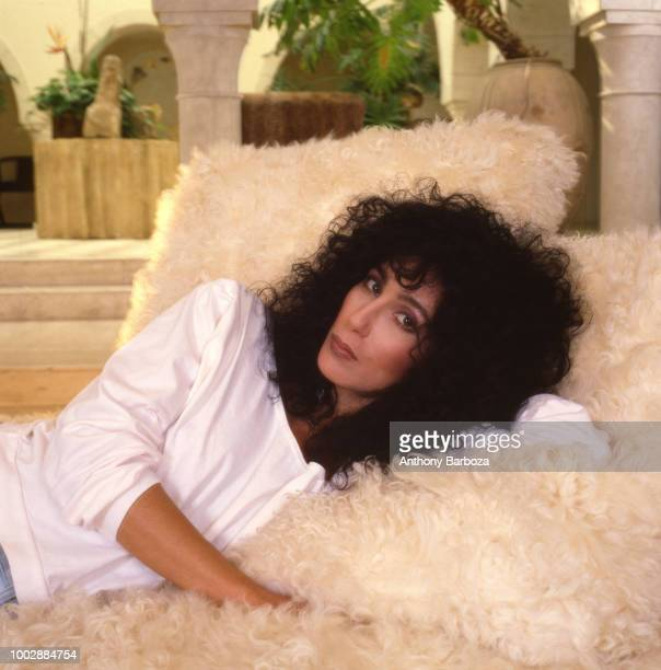 Portrait of American singer and actress Cher as she lies on a fuzzy couch Los Angeles California 1987