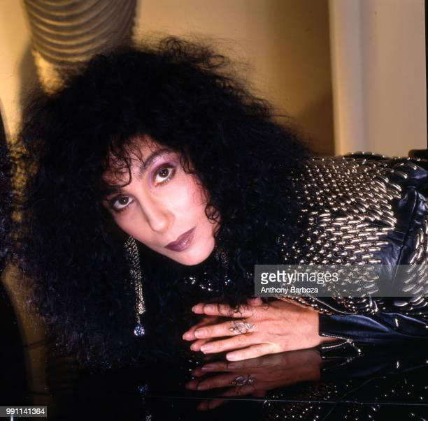 Portrait of American singer and actress Cher as she lies on reflective surface Los Angeles California 1987