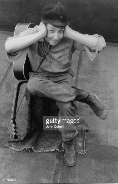 Portrait of American singer and musician Bob Dylan as he sits on a chair his guitar over his shoulder and comically covers his ears New York New York...