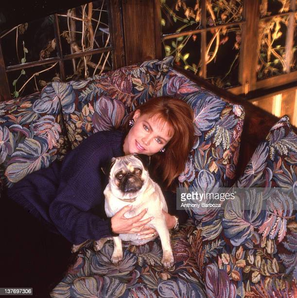 Portrait of American singer Belinda Carlisle as she poses with her dog on a couch in her home Beverly Hills California 1987