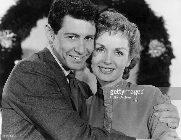 Portrait of American singer Eddie Fisher smiling and embracing his wife, American actor Debbie Reynolds, in front of a holiday wreath.