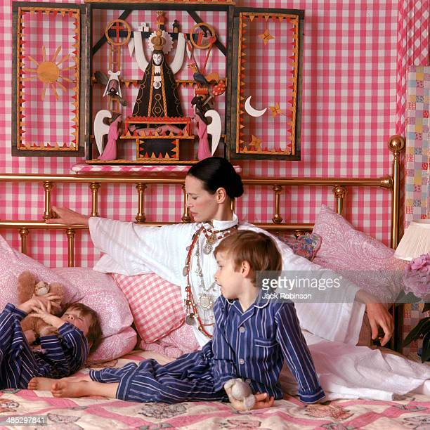 Portrait of American socialite and heiress Gloria Vanderbilt and her sons Anderson and Carter Cooper on a bed in their home Southampton Long Island...