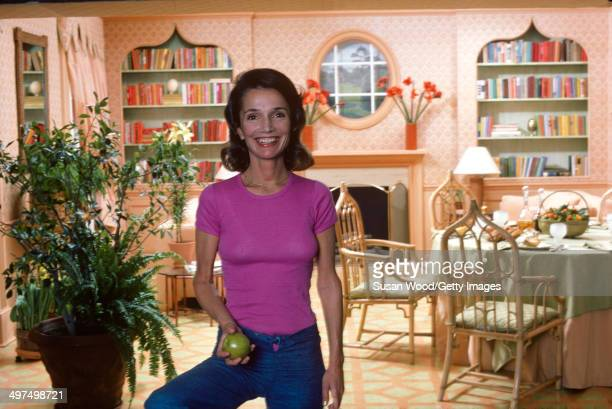 Portrait of American socialite Lee Radziwill as she poses with an apple in her dining room, March 1976.