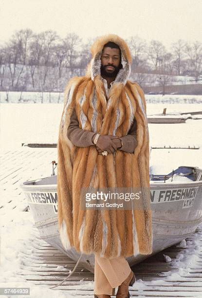 Portrait of American soul singer Teddy Pendergrass dressed in a fur coat and hood who stands on a dock with his hands clasped together in front of a...
