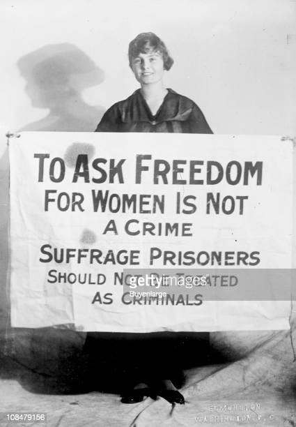 Portrait of American suffragist Lucy Gwynne Branham as she poses with a poster 1919 The poster reads 'To Ask Freedom for Women is Not a Crime...