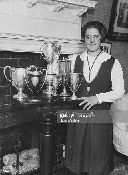 Portrait of American swimmer Gertrude Ederle with her trophies after breaking three World Records in Hawaii at her home in New York August 1926