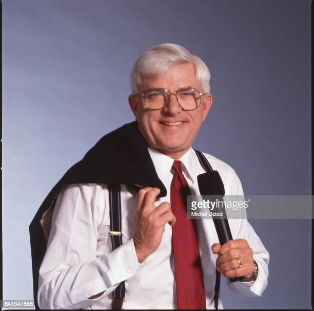 Portrait of American television personality Phil Donahue as he poses with his jacket over his shoulder and a microphone in one hand New York New York...