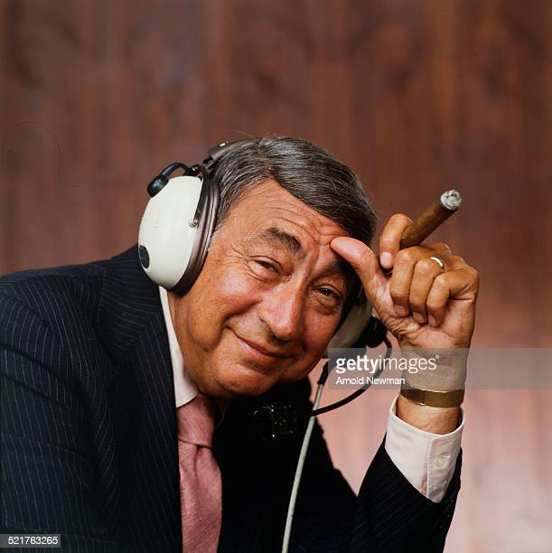 Portrait of American televison sports journalist Howard Cosell as he poses with a pair of headphones on his head and a cigar in his hand West Hampton...
