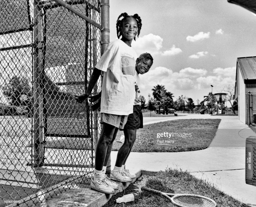 Portrait of American tennis players and sisters Venus Williams (left), 11, and Serena Williams, 9, as they hang onto the fence at the Compton tennis courts, South Central Los Angeles, California, April 20 1991. They had just complete a training session with their father and coach, Richard Williams.