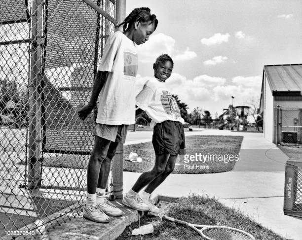 Portrait of American tennis players and sisters Venus Williams and Serena Williams as they hang onto the fence at the Compton tennis courts South...