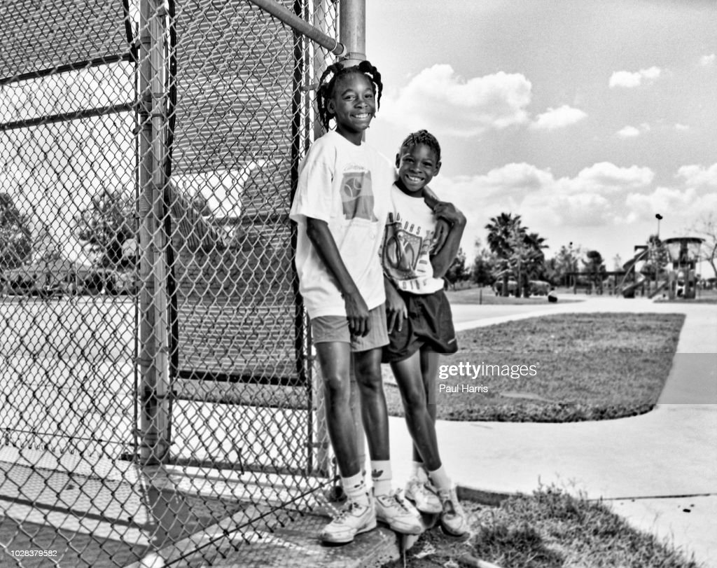 Portrait of American tennis players and sisters Venus Williams (left), 11, and Serena Williams, 9, as they pose beside the fence at the Compton tennis courts, South Central Los Angeles, California, April 20 1991. They had just complete a training session with their father and coach, Richard Williams.