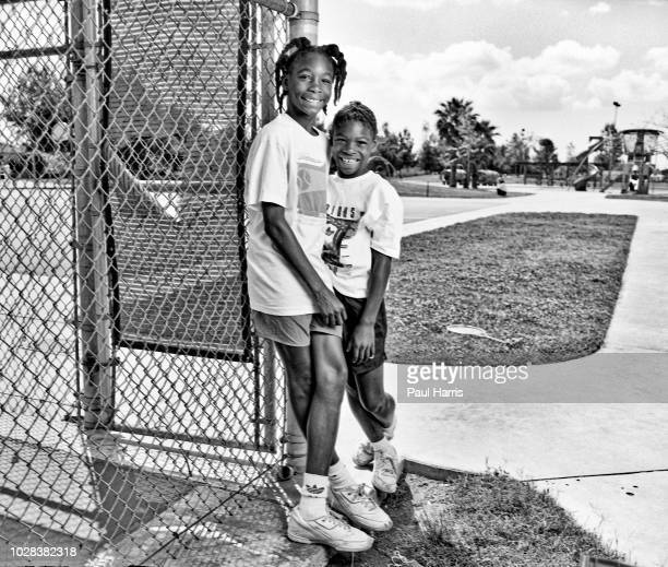 Portrait of American tennis players and sisters Venus Williams and Serena Williams as they pose beside the fence at the Compton tennis courts South...