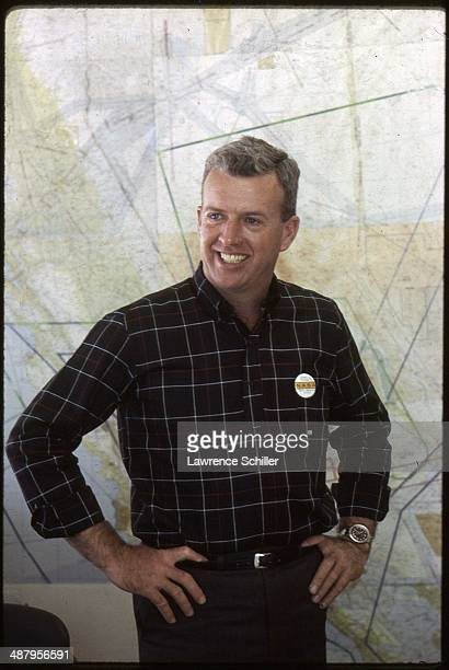 Portrait of American test pilot Joseph Walker as he stands hands on his hips in front of a number of maps on the wall at Edwards Air Force Base...