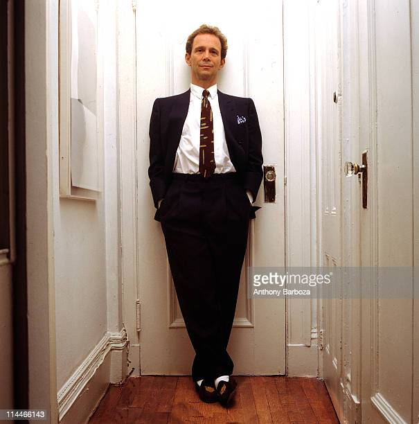 Portrait of American theatre and film actor Joel Grey, dressed in a suit with his hands in his pockets, as he leans against a closed door, New York,...