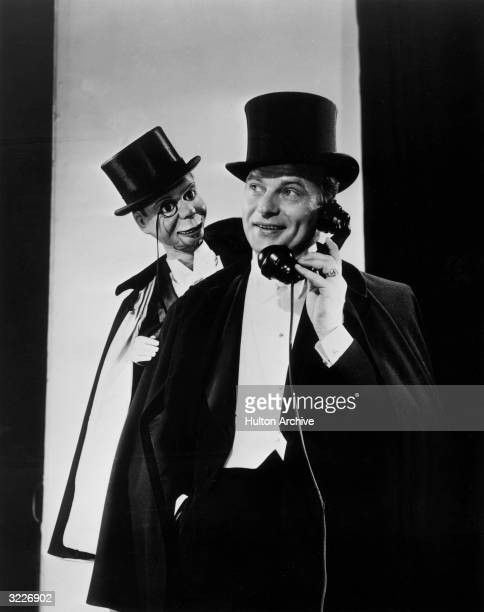 Portrait of American ventriloquist Edgar Bergen wearing a magician's costume with a top hat and talking on the phone while his dummy Charlie McCarthy...