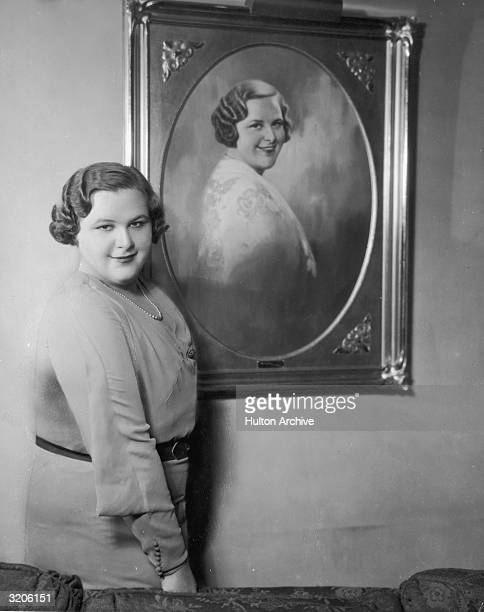 Portrait of American vocalist Kate Smith standing next to a painting of herself and smiling