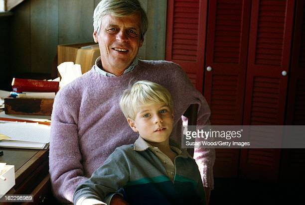 Portrait of American writer and journalist George Plimpton at his desk with his son, Taylor Ames Plimpton, in the paper-strewn writing studio at his...