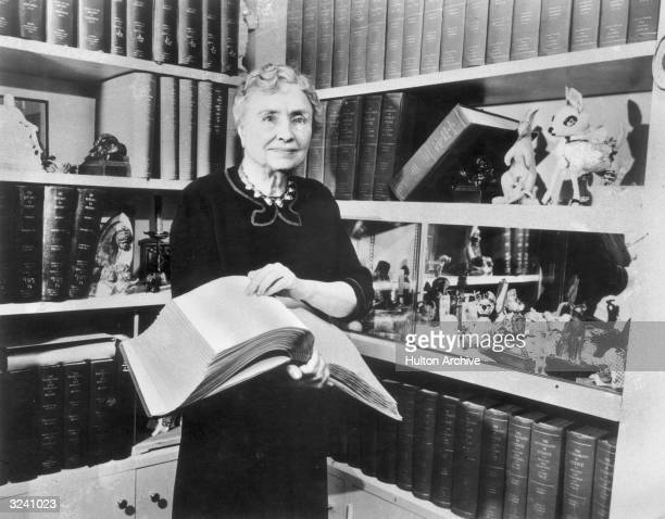 Portrait of American writer educator and advocate for the disabled Helen Keller holding a Braille volume and surrounded by shelves containing books...