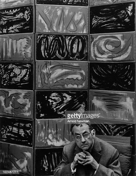 Portrait of Americanborn French artust Man Ray as he poses in front of a multipaneled painting Paris France Paris France May 1 1960