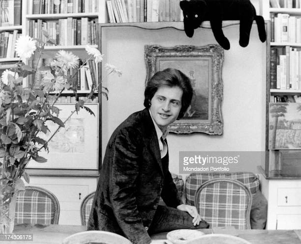 Portrait of Americanborn French singer Joe Dassin in front of a bookcase Behind him some paintings and a fluffy panther Paris 1970s