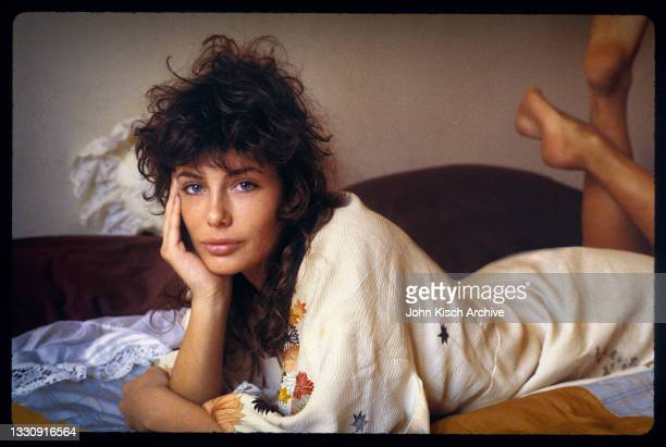 Portrait of American-British actress and model Kelly LeBrock, dressed in a robe, as she lays on a bed, her chin in her palm, New York, 1981.