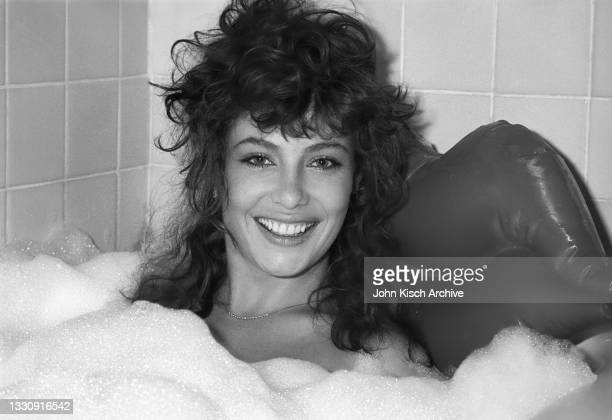 Portrait of American-British actress and model Kelly LeBrock, partially covered with soap bubbles, as she poses in a bathtub, New York, 1982.