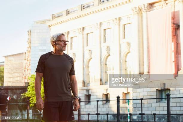 portrait of an active senior man doing exercise in the city of berlin - 50 54 years stock pictures, royalty-free photos & images
