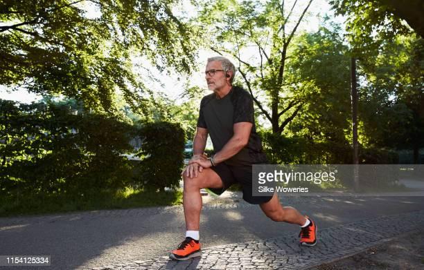 portrait of an active senior man doing exercise in the city of berlin - 55 59 jahre stock-fotos und bilder