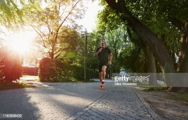 portrait of an active senior man doing exercise in the city of berlin - aktiver lebensstil stock-fotos und bilder