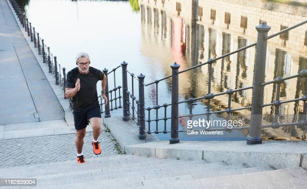 portrait of an active senior man doing exercise in the city of berlin - jogging stock pictures, royalty-free photos & images